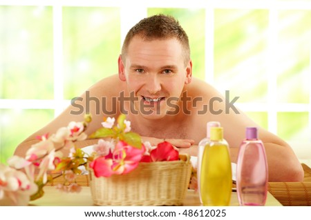 Man resting in sunny spa salon laying on the mat with flowers and cosmetics in foreground