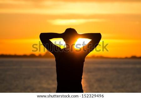 Man resting on the beach at sunrise - stock photo