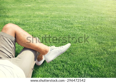 Man resting outdoor on a grass field - stock photo