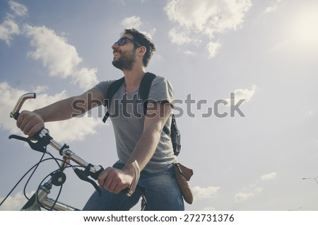 Man riding a bicycle in nature in retro style.