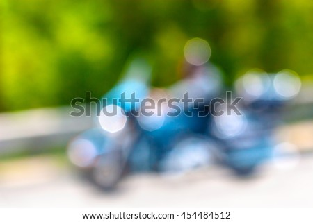 man riding a classic motorcycle in bokeh