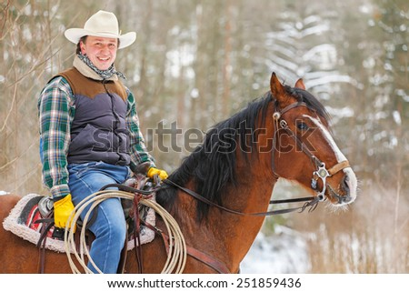 Man riding a horse in a winter forest. - stock photo