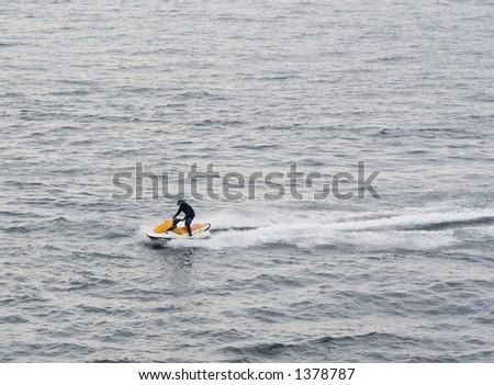 man riding a jet ski - thrill of aquatic sports - stock photo