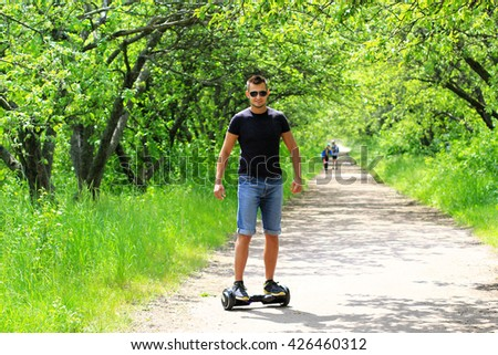 man riding an electronic scooter outdoors - personal portable eco transport, hover board, gyro scooter, hyroscooter, smart balance wheel