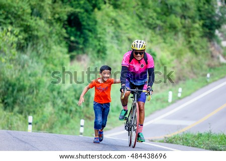 man riding bicycle go up the road on moutain at Ratchaburi province Thailand when 10-9-2016