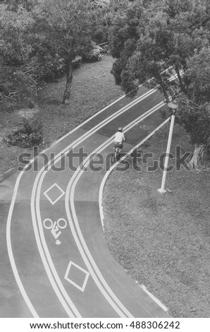 Man riding bicycle on the road. Man riding bicycle sign on the ground. Motion blur. Black and white image. Aerial view.