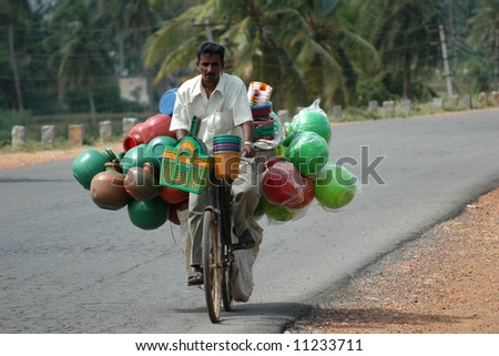Man riding bicycle to market with load of plastic water jugs - stock photo