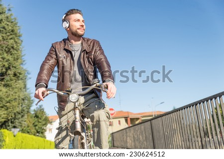 Man riding bike outdoors - Handsome young boy taking a tour bicycle and smiling - Vintage autumn look - stock photo