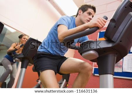 Man riding in a spinning class in gym - stock photo