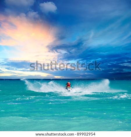Man riding jet ski in Caribbean sea - stock photo