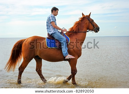 Man riding on a brown horse in a motion - stock photo