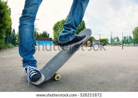 Man riding skateboard at skatepark, low angle view with fish eye lens. - stock photo