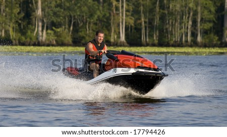 Man riding wave runner in river, enjoying a nice summer day.