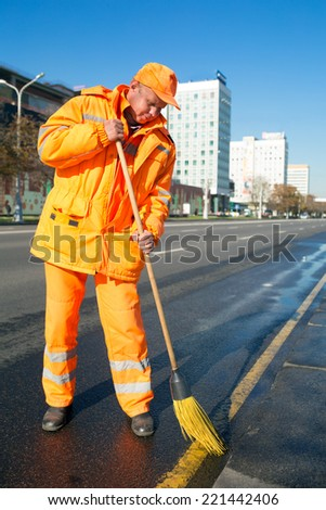 Man road sweeper worker cleaning city street with broom tool - stock photo