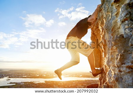 Man rock climbing up a steep mountain with copyspace - stock photo