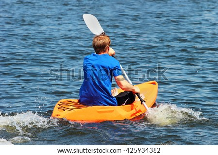 Man rowing a kayak across the blue waters - stock photo