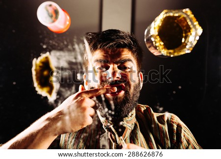 Man rubs cocaine on his gums to test quality. - stock photo