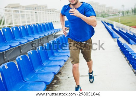 Man runner in blue shirt and shorts running between stands on stadium unrecognizable photo cropped by neck no face. Technique of running - stock photo