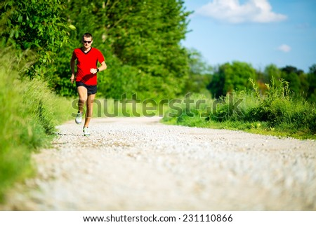 Man runner running on country road in summer sunset. Young athlete male training and doing workout outdoors in nature. - stock photo