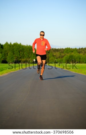 Man runner running on country road, training inspiration and motivation in summer sunset. Young athlete male training and doing workout outdoors in nature, sport and fitness lifestyle.