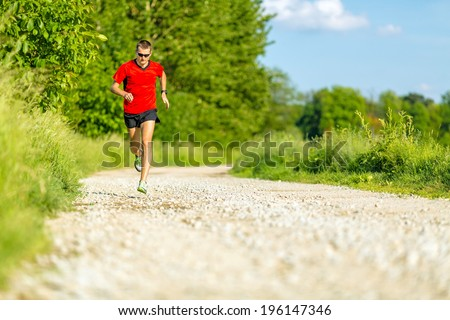 Man runner trail running on country road in summer sunset. Young athlete male cross country training and doing workout outdoors in green nature, summer blue sky - stock photo