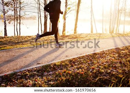 Man running at autumn during sunrise - stock photo