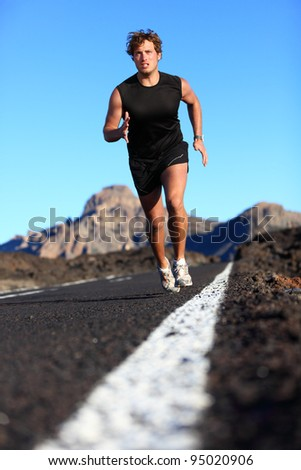 Man running in beautiful nature. Male runner jogging during work out training on mountain road. Young Caucasian fitness model with copy space. - stock photo