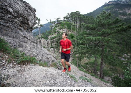 Man running in forest and mountains training and exercising for trail run marathon endurance race. Fitness healthy lifestyle concept with male athlete trail runner. - stock photo