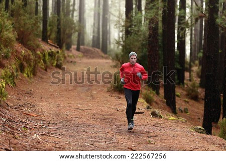Man running in forest woods training and exercising for trail run marathon endurance race. Fitness healthy lifestyle concept with male athlete trail runner. - stock photo