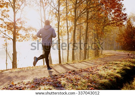 Man running in park at autumn morning. Healthy lifestyle concept - stock photo