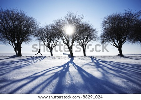 Man running in snow in winter landscape - stock photo
