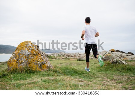 Man running in the coast in a cloudy day