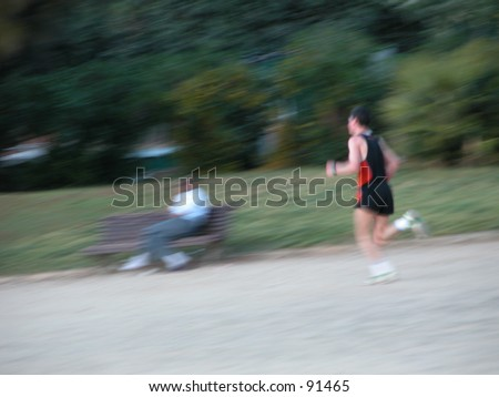 Man running in the park with person on a bench watching him (all blurred) - stock photo