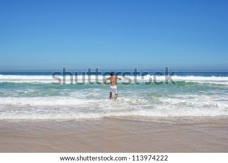 Man running in to indian ocean in south africa - stock photo
