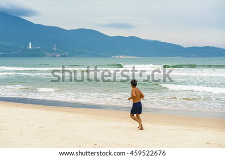 Man running near the China Beach in Danang in Vietnam. It is also called Non Nuoc Beach. South China Sea and Marble Mountains on the background.