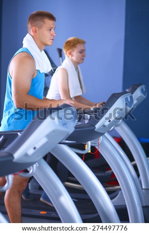 Man running on a treadmill in a fitness club - stock photo