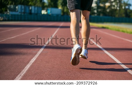 Man running on city stadium - stock photo
