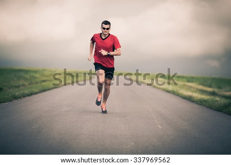 Man running on country road, healthy inspirational fitness lifestyle, sport motivation speed interval training. Runner jogging training and doing workout exercising power walking outdoors in nature. - stock photo