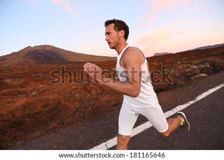 Man running on road in beautiful nature. Male runner sprinting during workout training for marathon on mountain road at night. Young Caucasian fitness model with copy space. - stock photo