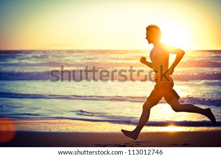 Man running on the beach at sunset - stock photo