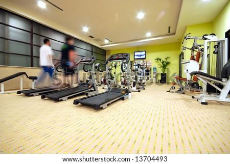 Man running on treadmill in gym - stock photo