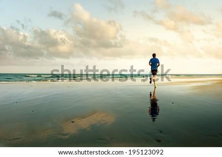 Man running on tropical beach at sunset. Maspalomas. Gran Canaria. - stock photo