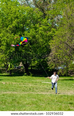 Man running over a green meadow in summer; he fly a kite