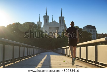 Man running towards Basilica of Notre-Dame de Fourvière in Lyon on a summer morning. Healthy lifestyle concept.