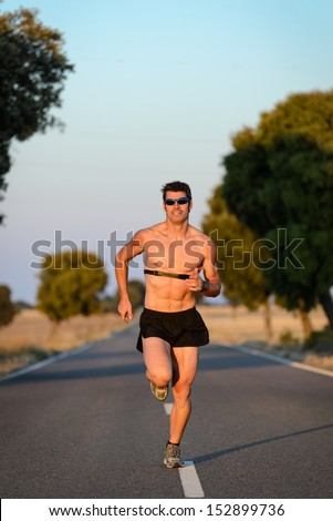 Man running with hearth rate monitor in countryside road. Fit naked muscular torso male athlete training for marathon run. - stock photo