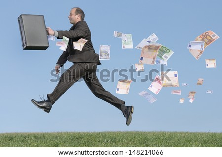 Man running with lots of money - stock photo