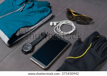 Man's accessories for sports. Tracksuit, smart phone with earphones, wristwatch, gloves and sunglasses