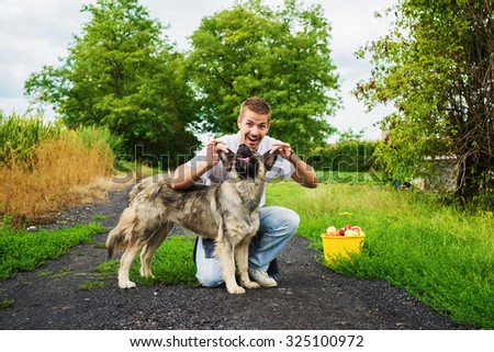 Man's best friend. Man holding dog's ears, looking at camera and smiling.