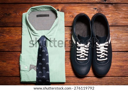 Man's collection of clothes in casual style consisting of a men's shirt with a tie and footwear on a wooden background - stock photo