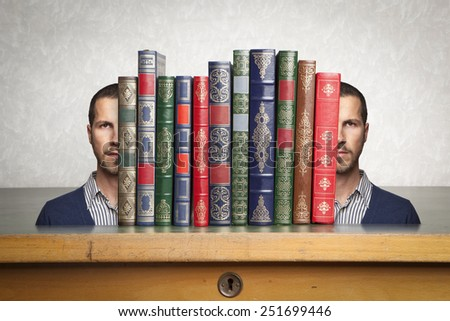 man's face split to hold a stack of books - stock photo